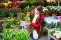 Beautiful young woman selecting flowers market