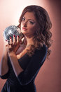Beautiful young woman with shiny ball in hands Royalty Free Stock Photos