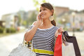 Beautiful young woman with shopping bags walking down the street Royalty Free Stock Photography