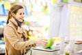 Beautiful young woman shopping for fruits and vegetables in produce department of a grocery store supermarket shallow dof color Stock Photography