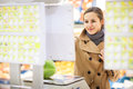 Beautiful young woman shopping for fruits and vegetables in produce department of a grocery store supermarket shallow dof color Royalty Free Stock Photo