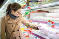 Beautiful young woman shopping for fruits and vegetables in produce department of a grocery store supermarket shallow dof color Royalty Free Stock Image