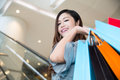 Beautiful young woman shopping in mall holding bags standing on escalator Stock Photos