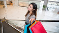 Beautiful young woman shopping in mall holding bags standing on escalator Stock Photography