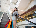 Beautiful young woman shopping in mall holding bags standing on escalator Royalty Free Stock Images