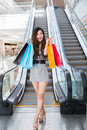 Beautiful young woman shopping in mall holding bags standing on escalator Royalty Free Stock Photo