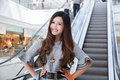Beautiful young woman shopping in mall holding bags standing on escalator Stock Image