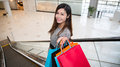 Beautiful young woman shopping in mall holding bags standing on escalator Stock Photo