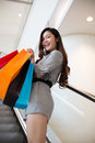 Beautiful young woman shopping in mall holding bags standing on escalator Royalty Free Stock Image
