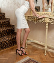 Beautiful young woman in short white tight fit skirt and corset looking into mirror. Perfect body female in front of a mirror Royalty Free Stock Photo