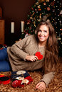 Beautiful young woman showing a heart in front of the christmas tree Royalty Free Stock Photography