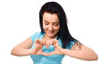 Beautiful young woman showing heart symbol gesture isolated over white background Stock Photography
