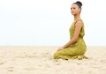 Beautiful young woman sitting alone on sand at the beach horizontal portrait of a Royalty Free Stock Photos