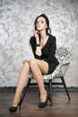 Beautiful young woman sitting in a armchair. Black dress, shoes and stockings Royalty Free Stock Photo