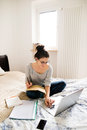Beautiful young woman sitting on bed, working. Home office. Royalty Free Stock Photo
