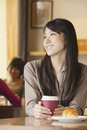 Beautiful young woman sitting at a coffee shop looking away Stock Photo