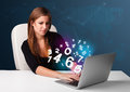 Beautiful young woman sitting at desk and typing on laptop with d numbers comming out Royalty Free Stock Image