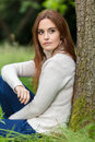 Beautiful Young Woman Sitting Leaning Against Tree Royalty Free Stock Photo