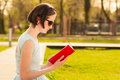 Beautiful young woman sitting in the park and reading a book as recreation concept Royalty Free Stock Images