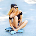 Beautiful young woman sitting on a skateboard outdoor Stock Photography