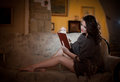 Beautiful young woman sitting on sofa holding a book, vintage scenery. Attractive brunette girl with long hair and long legs Royalty Free Stock Photo