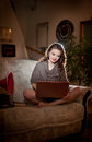 Beautiful young woman sitting on sofa working on laptop having a red gramophone near her in boudoir scenery attractive brunette Stock Images