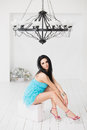 Beautiful young woman sitting on a suitcase in room with black chandelier Royalty Free Stock Photo