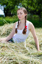 Beautiful young woman sitting thoughtful on dry hay on summer day closeup Stock Photography