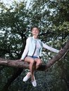 Beautiful young woman sitting on a tree branch in spring garden Royalty Free Stock Photo