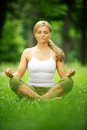 Beautiful young woman sitting in yoga pose in the park portrait of a Stock Image