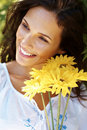 Beautiful young woman smiling with yellow flowers Royalty Free Stock Image