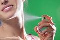 Beautiful young woman spraying parfume