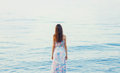 Beautiful young woman standing near sea, back female Royalty Free Stock Photo