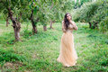 Beautiful young woman is standing between the trees