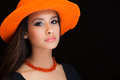 Beautiful young woman studio portrait wearing a orange colored hat on a black background Stock Photography