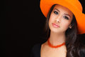 Beautiful young woman studio portrait wearing a orange colored hat on a black background Stock Photo
