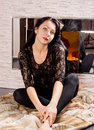 Beautiful young woman stylish black outfit sitting front fire fur coat floor Stock Photos