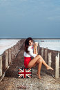 Beautiful young woman with suitcase with british flag outdoor portrait of sitting on holding cup Stock Images