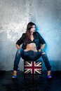 Beautiful young woman with suitcase with british flag portrait of casual metal wall as a background Stock Photo