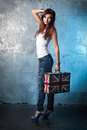 Beautiful young woman with suitcase with british flag portrait of casual metal wall as a background Stock Image