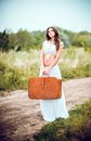Beautiful young woman with suitcase in hands stands on rural road a Royalty Free Stock Image