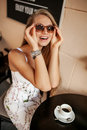 Beautiful young woman in sunglasses in cafe smiling Royalty Free Stock Photo