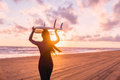 Beautiful young woman surf girl in wetsuit with surfboard on a beach at sunset or sunrise and ocean Royalty Free Stock Photo