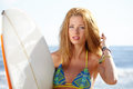 Beautiful young woman surfer girl in bikini with surfboard at a beach Stock Photo