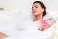 Beautiful young woman takes bubble bath brunette Stock Image