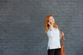 Beautiful young woman talking on smart phone with purse Royalty Free Stock Photo