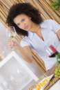 Beautiful young woman tasting white wine in wine cellar