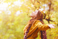 Beautiful young woman throwing leaves in a park Royalty Free Stock Photo