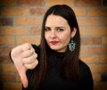 Beautiful young woman with thumb down. Royalty Free Stock Photo