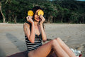 Beautiful young woman tourist In a striped swimsuit holding two ripe pineapple against her eyes.